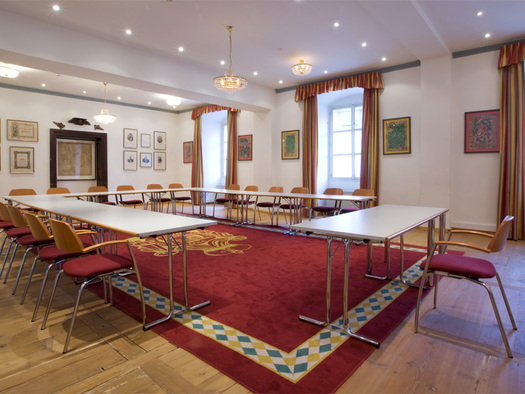 Holzboden, Teppich, Tische und Stühle, Viele Bilder hängen an der Wand, große Fenster im Hintergrund. (© Schloss Mondsee)