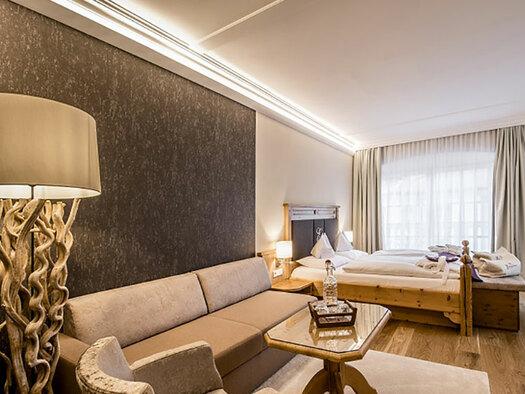 Linke Lampe, Couch und Tisch, im Hintergrund Doppelbett und Flachbildschirm, Holzboden. (© Karin Lohberger)