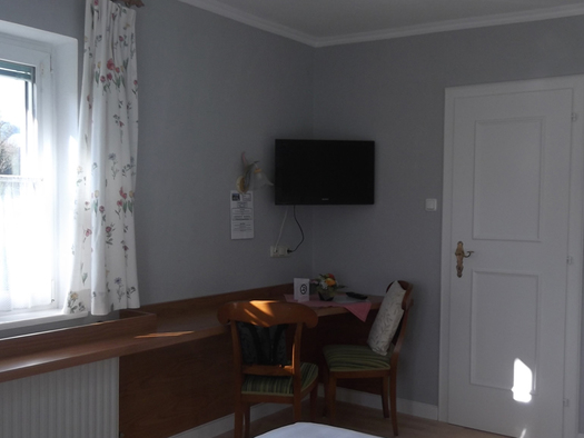 Schlafzimmer: mit Fernseher, Tisch und Stühle, seitlich ein Fenster. (© Knoblechner)