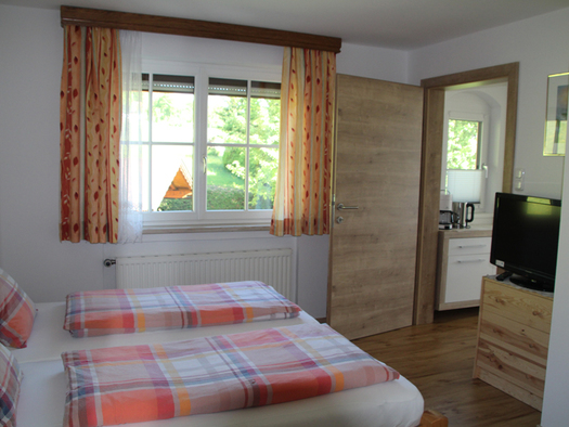 double bed, TV, background a window. (© Tourismusverband MondSeeLand)