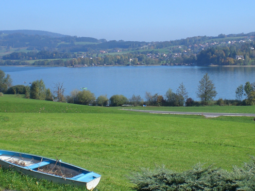 In front of the window n the lawn lies a paddle boat, behind the lake and mountains are visible. (© Bauernhof Schink)
