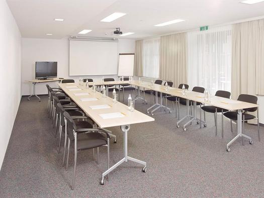 Tisch und Stühle in U-Form aufgestellt, im Hintergrund Fernseher, Flipboard, Leinwand, Beamer an der Decke. (© Jugendgästehaus)