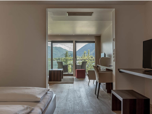View through the lake suite with double bed, table, chairs, stool, on the terrace chairs and table overlooking the countryside, the lake and the mountains. (© Lackner)