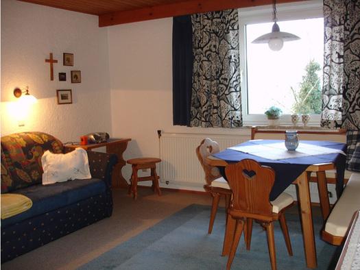 Wohnbereich mit Couch, Polster, Hocker, seitlich Eckbank mit Tisch und Stühle, im Hintergrund ein Fenster. (© Familie Laireiter)