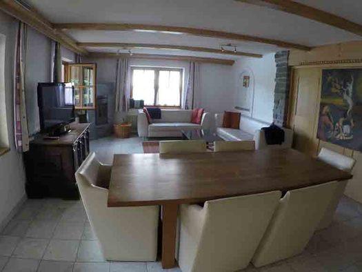 Tisch mit Stühlen, seitlich Kommode mit Fernseher, im Hintergrund Couch, Fenster. (© Wiener)