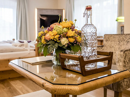 in the front table with chair, on the table water and flowers, in the Background doublebed and flatscreen. wooden floor. (© Karin Lohberger)