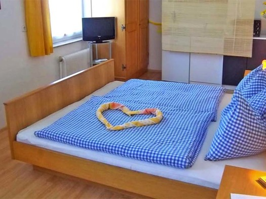 Schlaf- Wohnbereich mit Doppelbett, TV, im Hintergrund die Kochgelegenheit. (© Gästehaus Horizont)