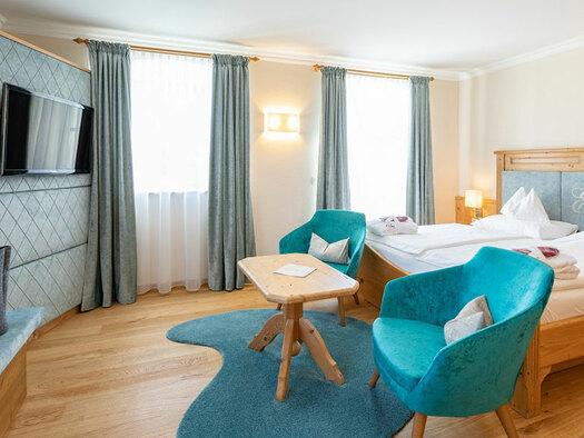 Doppelbett mit 2 Sessel und Tisch, TV an der Wand, kleine Bank an der Seite mit 2 grauen Taschen darauf. (© Eichingerbauer)