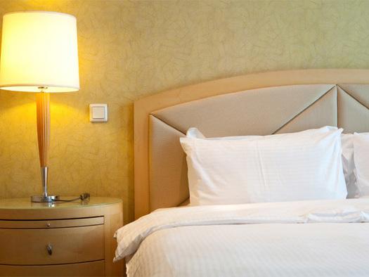 Doppelbett mit Nachtkästchen und Tischlame. (© 1)