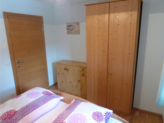 Sleeping room with a doublebed-end infront, in the Background a wardrobe and a dresser, on the rigth side the door. (© Mayrhofer)
