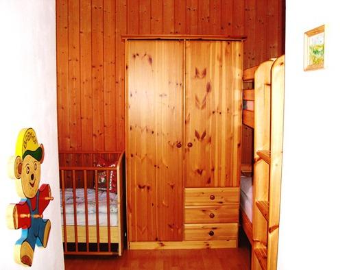 Kinderzimmer mit Gitter- und Etagenbett
