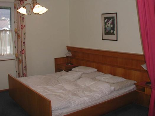 Schlafzimmer mit Doppelbett, Nachtkästchen, hinter dem Bett ein Bild, im Hintergrund ein Fenster, Teppichboden. (© Knoblechner)