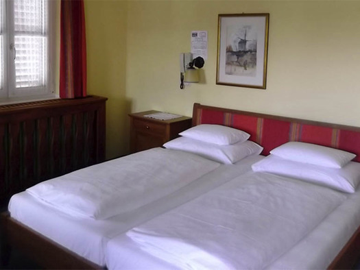 Schlafzimmer mit Doppelbett, Nachtkästchen, hinter dem Bett ein Bild und Telefon auf der Wand, seitlich ein Fenster. (© Knoblechner)