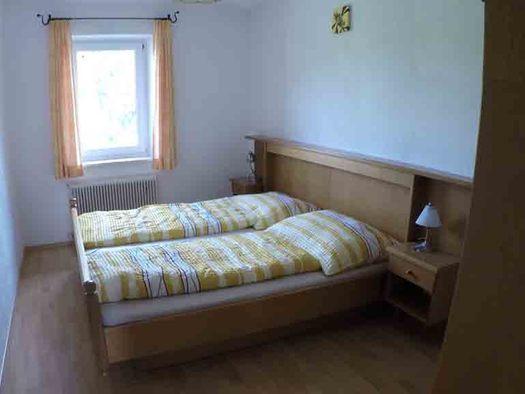 Schlafzimmer mit Doppelbett, Nachtkästchen, Tischlampe, im Hintergrund ein Fenster. (© Wiener)