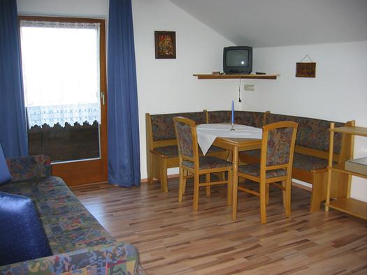Essbereich mit Eckbank, Tisch und Stühle, seitlich eine Couch, im Hintergrund eine Balkontür. (© Winter)