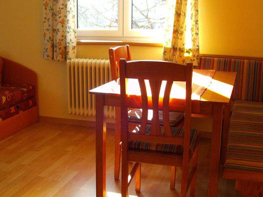 Wohnbereich, Eckbank, Tisch und Stühle, seitlich eine Bank, im Hintergrund ein Fenster. (© Stabauer)