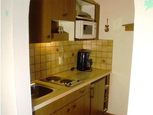 Küche mit Spüle, Herdplatte, Kaffeemaschine, Mikrowelle. (© Pichler)