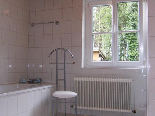 bathroom with tub and stool, window in the background. (© Maier)