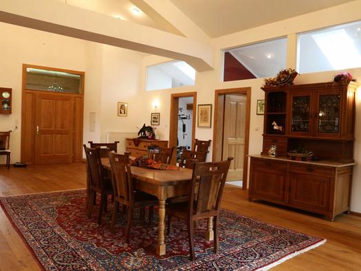 Blick in den Wohnbereich mit Tisch und Stühle, Holzboden, Teppich. (© Familie Radauer)