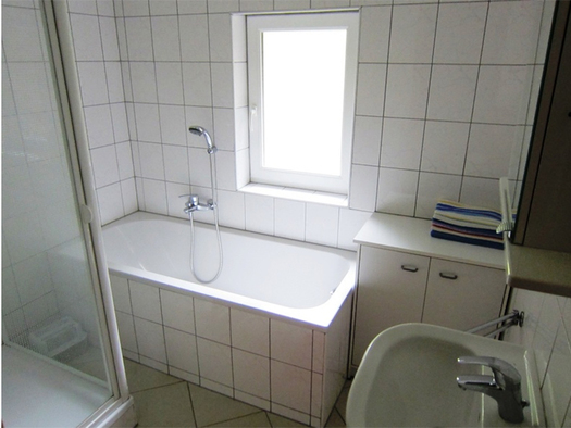 On the side a sink, behind it a small cupboard, beside it a bathtub, part of the shower sideways, in the background a window. (© Weber)