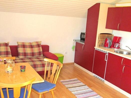Blick auf die Küche und Essgelegenheit, mit Tisch und Stühlen, in der Ferienwohnung Drachenwand, im Hintergrund eine Couch. (© Gästehaus Horizint)