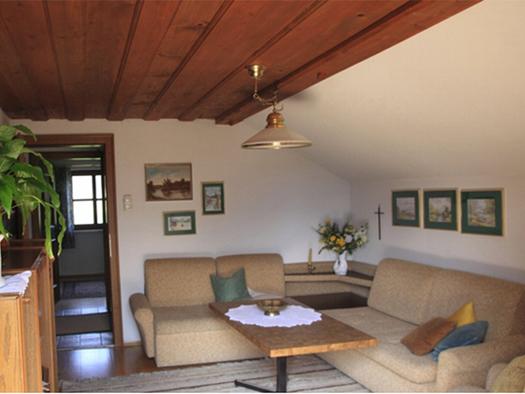 Couch, Tisch, seitlich eine Kommode mit einem Blumenstock, Bilder an der Wand. (© Edtmayer)