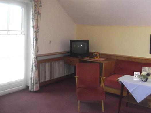 Sessel, Tisch und Bank, Fernseher steht im Eck, seitlich eine Balkontür, Teppichboden. (© Knoblechner)