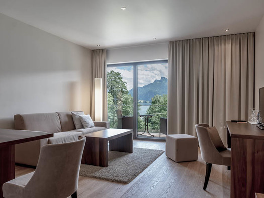 Living room, table and chair, sofa, stool, table with TV, in the background view through the balcony to the terrace with table and chairs, view to the lake and to the mountains. (© Lackner)