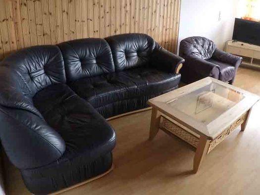 Wohnbereich mit Ledercouch, Sessel, Tisch im Hintergrund Fernseher, Hocker, Fenster. (© Wiener)