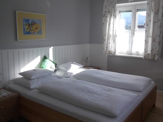 Schlafzimmer mit Doppelbett, Nachtkästchen mit Tischlampen, hinter dem Bett ein Bild, im Hintergrund ein Fenster. (© Knoblechner)