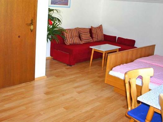 Blick in den Wohnbereich, Doppelbett, Couch, Tisch und Stühl. (© Gästehaus Horizont)