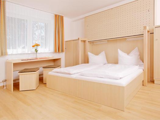 Schlafzimmer mit Doppelbett, Schränke, seitlich ein länglicher Tisch mit Hocker und Fenster. (© Jugendgästehaus)