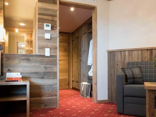 Blick von einem Hotelzimmer Richtung Vorraum und Tür, auf der Seite sieht man einen Tisch mit Sofa, auf der anderen Seite das Nachtkästchen und einen Teil des Bettes. (© www.mondsee.at)