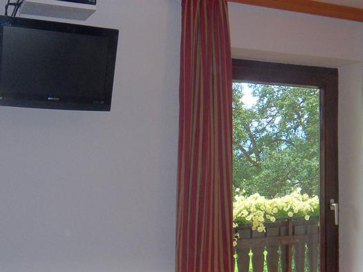 Fernseher hängt auf der Wand, daneben eine Balkontür. (© Schafleitner-Kroiß)