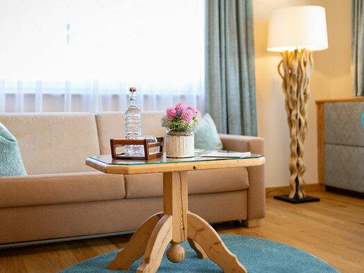 Couch mit Tisch darauf Flasche und Blumen, Stehlampe. (© Eicherbauer)