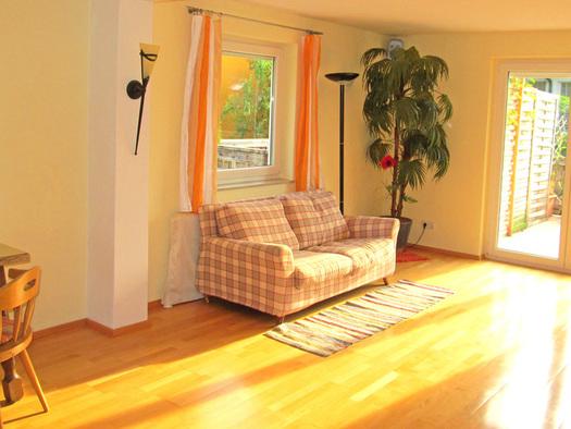 Wohnbereich mit einer Couch, Tisch und Stuhl. (© Gästehaus Horizont)