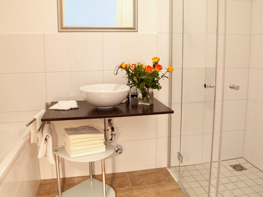 bathroom with tub, shower, sink in the background, nearby the sink is a vase with flowers, mirror. (© Wieneroither)