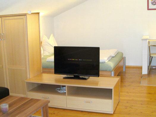 im Hintergrund Doppelbett, Tisch, Stuhl, im Vordergrund ein Kleiderschrank, Fernseher, Couch und Tisch. (© Stabauer)