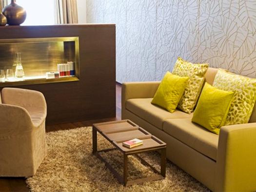Blick in den Wohnbereich mit Sofa, Tisch und Sessel, im Hintergrund eine Kommode. (© Hotel Iris Porsche)