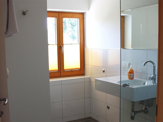 look at the bathroom with sink and Soap, window in the background. (© Schnöll)