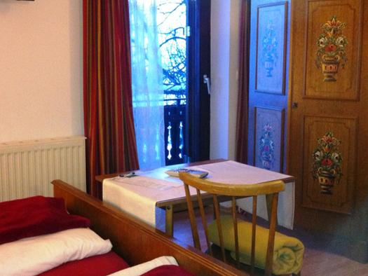 Schlafzimmer, im Vordergrund sieht mein einen kleinen Teil vom Doppelbett, dahinter ein Tisch mit Stühlen, Kleiderschrank und eine Balkontür. (© Schafleitner-Kroiß)