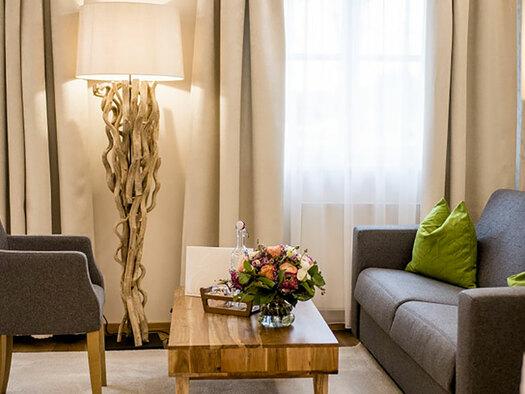 Sitzecke mit Couch, Tisch und Fauteuil, im Hintergrund Stehlampe und Balkontüren. (© Karin Lohberger)