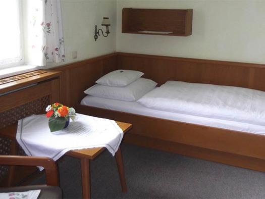 Schlafzimmer mit Einzelbett, seitlich ein Fenster und ein Tisch, Teppichboden. (© Knoblechner)