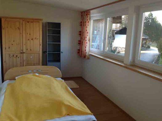 Schlafzimmer mit Einzelbett, im Hintergrund ein Kleiderschrank, Regal, seitlich Fensterfront. (© Wiener)