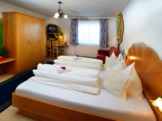 Schlafzimmer mit Doppelbett, im Hintergrund Couch, Fenster, Fernseher, seitlich ein Kleiderschrank. (© Stabauer)