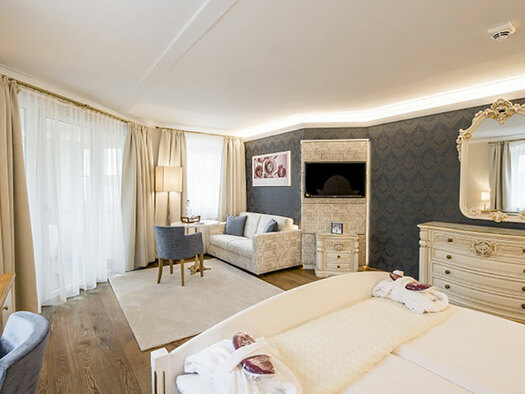In the front end of the doublebed, right dresser with mirror, flatscreen, in the backside couch, table and Fauteuil and doors to the balcony. (© Karin Lohberger)