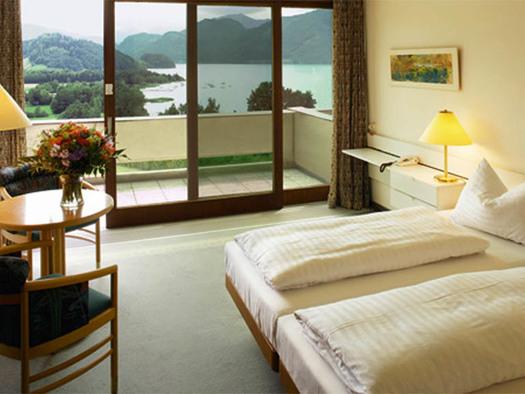 Zimmer mit Doppelbett, Tischlampe, Telefon, seitlich ein Tisch mit Stühlen, Fernseher, im Hintergrund eine große Balkontür mit Blick auf den See und die Landschaft. (© Landzeit)
