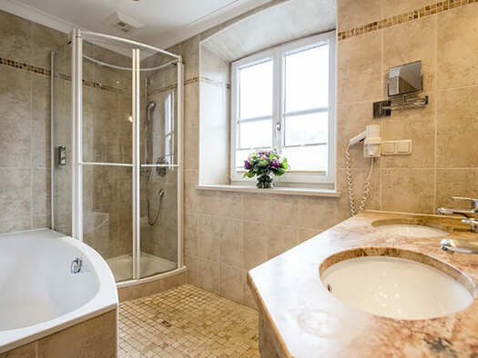view into the bathroom with right the lavatory, in the background the shower, right a tub. (© Karin Lohberger)