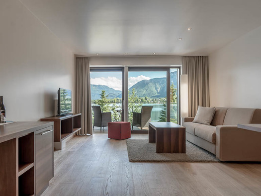 Chest of drawers / table, sideboard with TV, stool, table, couch, in the background view through the large balcony to the terrace with chairs and table, landscape, lake, mountains. (© Lackner)