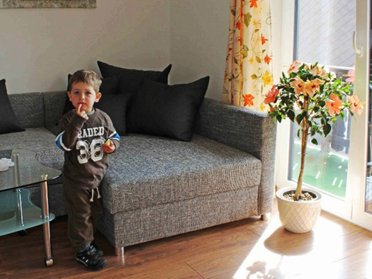 Living area with a big sofa, in front a child. (© Knoblechenr)